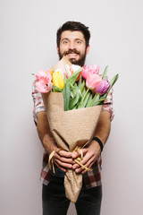 Handsome young man with beard  pointed on camera nice bouquet of flowers against white background