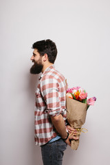 Side Handsome young man with beard  and nice bouquet of flowers against white background