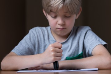 Sad boy doing a drawing