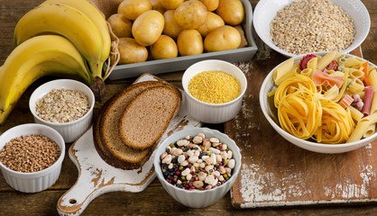 Foods high in carbohydrate on a rustic wooden table.