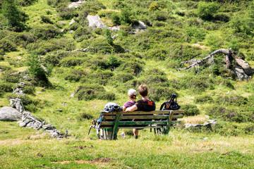 ein Paar erholt sich von einer Bergwanderung auf einer Bank