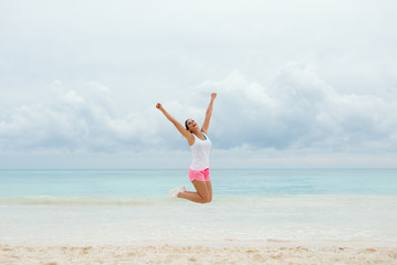 Fitness happy woman jumping for celebrating workout success and summer vacation freedom at the beach.