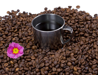 flower and steel cup of coffee in coffee grains
