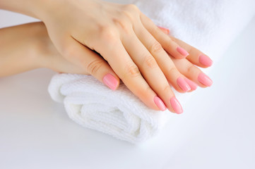 Foto auf Leinwand Maniküre Hands of a woman with pink manicure are on a towel