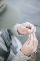 A person's hands tying a fishing fly onto a hook,