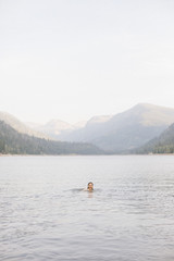 A woman swimming in the waters of a lake,