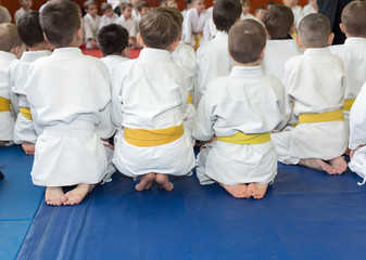Foto auf AluDibond Kampfsport Children in kimono sitting on tatami on martial arts seminar. Selective focus