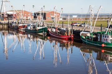 Fischkutter reflektieren in ruhigem Hafenwasser