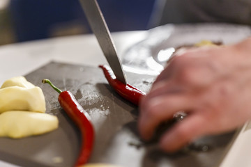Man slicing Chilli pepper with Knife on chopping board