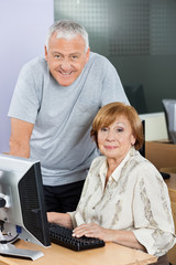 Happy Senior Man And Woman At Computer Desk In Classroom