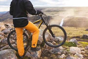 Happy biker on backdrop of waterfall in mountains. Iceland