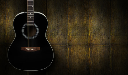 Black acoustic guitar on dark yello wooden background.
