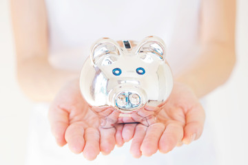 woman holding white piggy bank over body background.