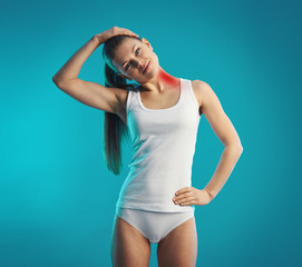 Young woman exercising neck, stretching left side of her body. Concept of neck pain, back injury and therapy.