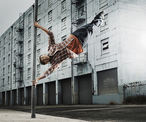 Young man breakdancing, leaping in air, and stretching out