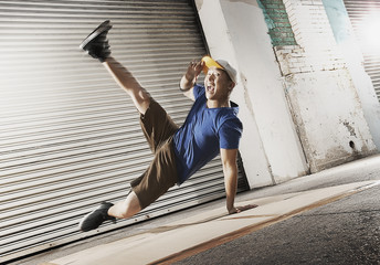 A young man breakdancing on the street of a city, balancing on one hand with his legs apart,