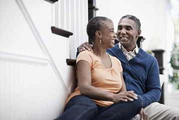 A mature couple, man and woman, sitting on the stairs together at home,