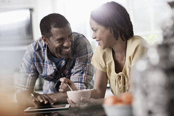 A man and woman, couple in their kitchen both looking at a digital tablet,