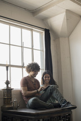 Loft living, A man and woman sitting by a window using a digital tablet,
