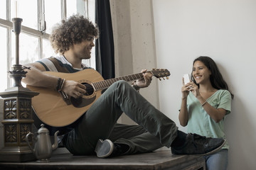 Loft living, A young man playing guitar to an appreciative audience, a young woman holding a smart phone and taking a photograph,