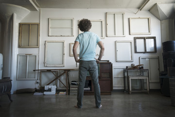Loft decor, A wall hung with pictures in frames, reversed to show the backs, A man with hands on his hips looking at the wall,