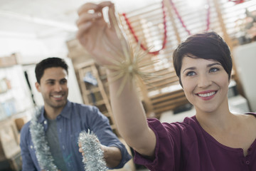 Christmas decorations, A man and woman holding tinsel and decorations,