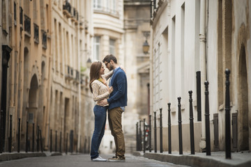 A couple standing gazing at each other, in a narrow street in a city,