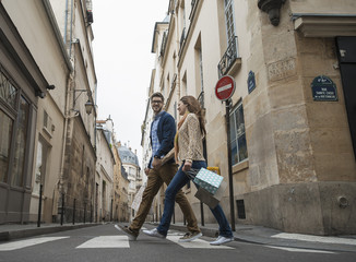 A couple walking along a narrow street in a historic city centre, with shopping bags,