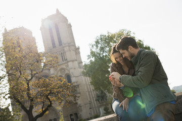 A couple side by side looking a  smart phone screen outside Notre Dame cathedral in Paris,