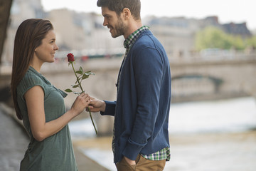 A couple in a romantic setting by a river, A man offering a woman a red rose,