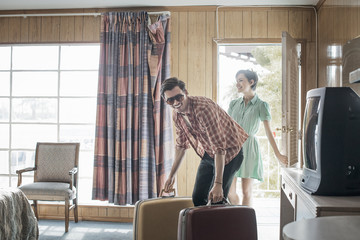 A young couple arriving in a motel room,