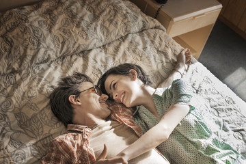Young couple lying side by side on top of  bed in motel room