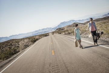 A young couple, man and woman walking hand in hand on a tarmac road in the desert carrying cases,