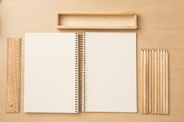 Less is more, Notebook with  color pencils and ruler on a table, flat top view