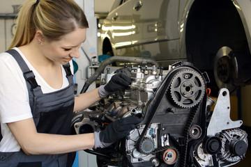 Frau als Kfz-Mechaniker bei Reparatur von Motor in Autowerkstatt