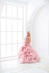 Pregnancy woman in magnificent last pink princess dress near window