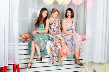 Three young, beautiful and emotion girls in bright colored dresses. Decoration flowers and heart.  Spring mood - smile and antics