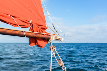 wooden boom of vintage sailing boat with an ocher sail, ropes, upper works and pulley during a sunny sea trip