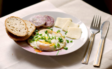 light breakfast on the table with egg, bread, cheese and sausage