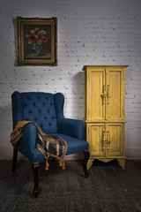 Vintage blue armchair, yellow cupboard and framed painting