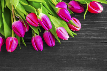 Spring pink tulips bouquet over wooden background