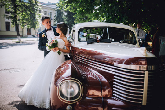 Happy bride and groom hugging and posing near old retro car