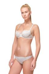 Young blonde woman in white underwear, studio
