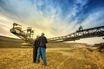 Two coal mine engineers with protective helmets standing in front of huge drill machine, chatting and watching at the digging site. Beautiful and colorful sky in the background. Rear view.