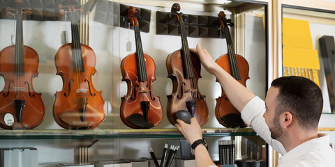Door stickers Music store Positive man purchasing traditional violins in store