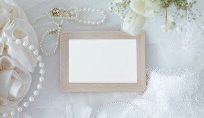 Blank wooden frame with flowers, jewelry, fur and accessories on white cloth background