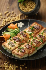 Pan fried tofu with garnish served on a plate