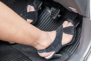 A woman's foot with high heels pressing the accelerate pedal of a car