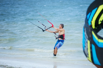 Male kitesurfer looking up at the kite and holding a bar