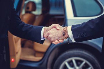 Business men handshake near the car.
